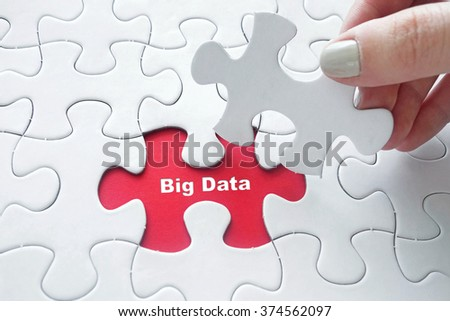 Close up of girl's hand placing the last jigsaw puzzle piece with word Big Data as Data Concept - stock photo