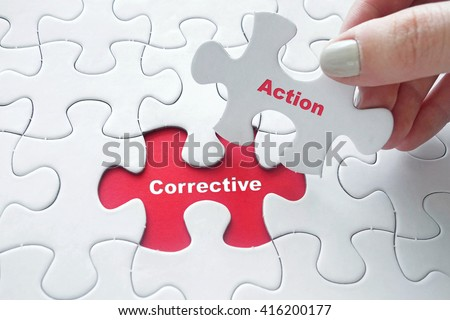 Close up of girl's hand placing the last jigsaw puzzle piece with word Corrective Action - stock photo
