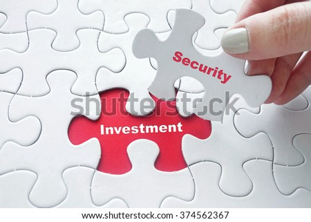 Close up of girl's hand placing the last jigsaw puzzle piece with word Investment and Security as Investment Security concept - stock photo