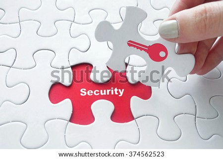 Close up of girl's hand placing the last jigsaw puzzle piece with word security and key icon as security concept - stock photo