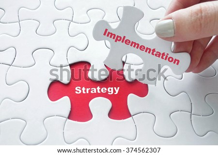 Close up of girl's hand placing the last jigsaw puzzle piece with word Strategy Implementation as business concept - stock photo