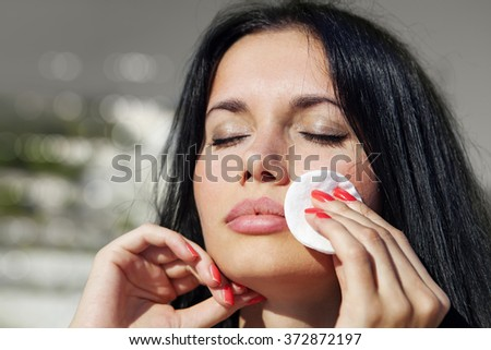 close up of girl who cleans her face by tonic - stock photo