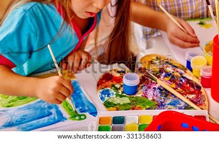 Close up of girl with brush painting on table in  kindergarten . - stock photo