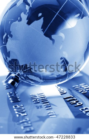 Close-up of glass globe on credit cards. Toned monochrome image. Shallow DOF. - stock photo