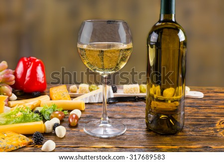 Close Up of Glass of White Wine with Bottle on Rustic Wooden Table Surrounded by Variety of Cheeses and Fresh Fruit - stock photo