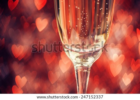 Close up of glass with champagne over abstract defocused lights shaped like hearts - stock photo