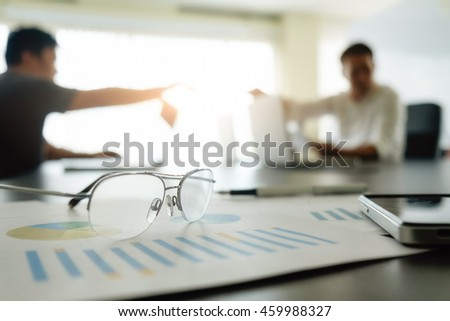 Close up of glasses and smart phone on charts with asian business people discussing the charts and graphs showing the results of their successful teamwork background,selective focus. Business concept. - stock photo