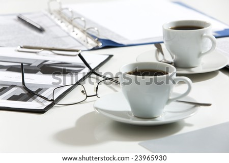 Close-up of glasses, documents, pen, cups of coffee on the table - stock photo