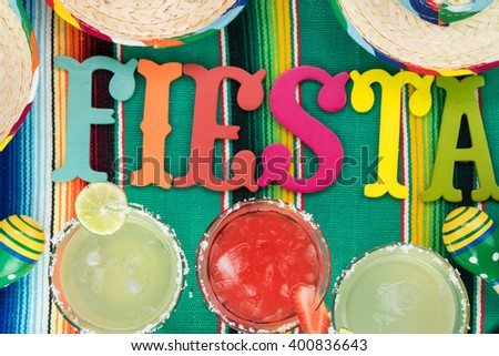 Close up of glasses of margarita cocktail garnished with salt rim and lime and strawberry on fiesta decorated table. - stock photo