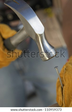 Close-up of gloved hands hammering a nail - stock photo