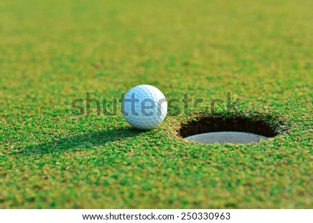 Close up of golf ball near the hole - stock photo