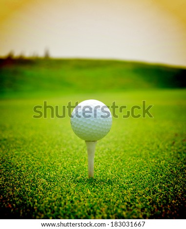 Close up of golf ball with tee on grass - stock photo