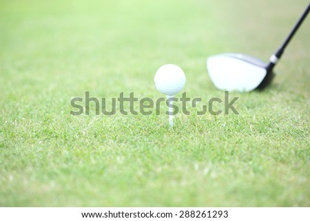 Close-up of golf club and tee with ball on grass - stock photo