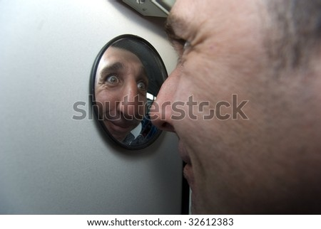Close up of goofy man looking in mirror - stock photo