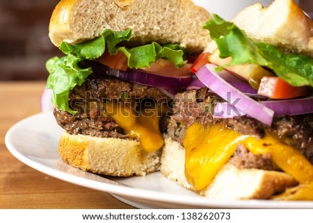 Close up of gourmet cheeseburger with melted cheese, tomatoes, lettuce and onions sitting on white plate - stock photo