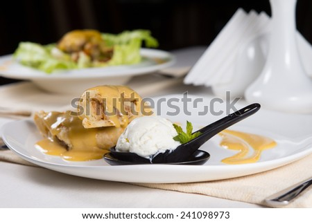 Close Up of Gourmet Dessert Crepes with Scoop of Ice Cream Served on Restaurant Table - stock photo