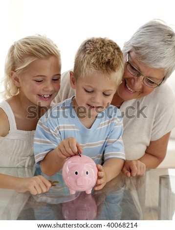 Close-up of grandmother and children saving money in a piggy bank - stock photo