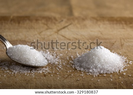 Close-up of granulated sugar in silver spoon and one pile of white sugar - stock photo