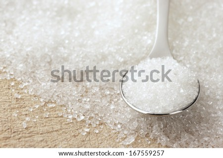 Close-up of granulated sugar in spoon and sugar pile. - stock photo