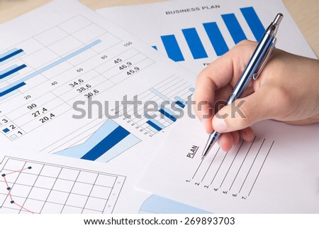 close up of graphs and charts analyzed by businessman - stock photo