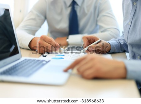 Close-up of graphs and charts analyzed by businesspeople - stock photo