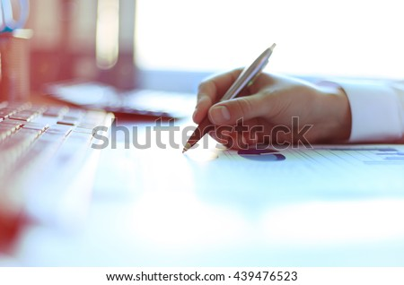 Close-up of graphs and charts analyzed by businesswoman  - stock photo