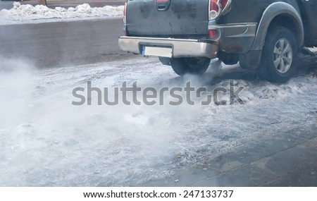 Close-up of gray car exhaust pipe with smoke  - stock photo