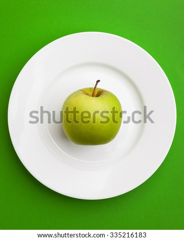 Close-up of green apple on white plate.  - stock photo