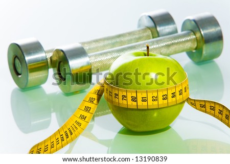 Close-up of green apple tied with measuring tape on the background of dumbbells - stock photo