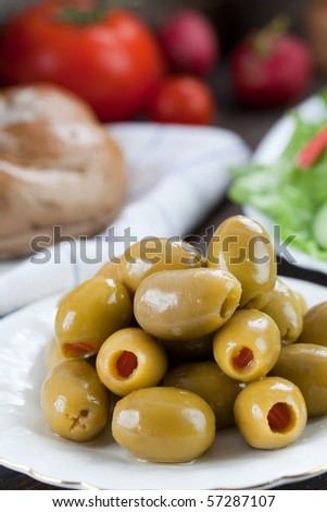 Close up of green olives in small plate with some other food on the background - stock photo