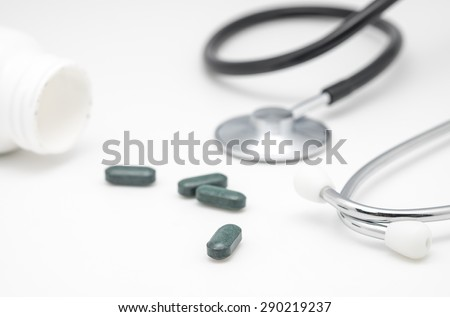 Close up of green pills or vitamin with stethoscope on white for medical and health care background  - stock photo