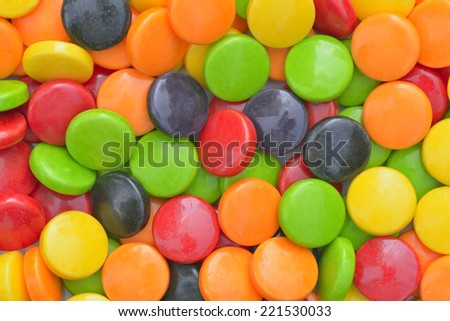 Close-up of green, yellow, red, orange and black round candies  - stock photo