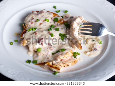 Close up of grilled chicken breast under cream and milky cheese sauce on white plate on dark wood background - stock photo