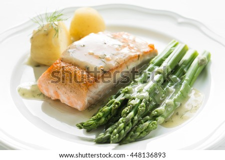 Close up of grilled salmon fillet with potatoes and asparagus garnished with dill sauce arranged on white plate - stock photo