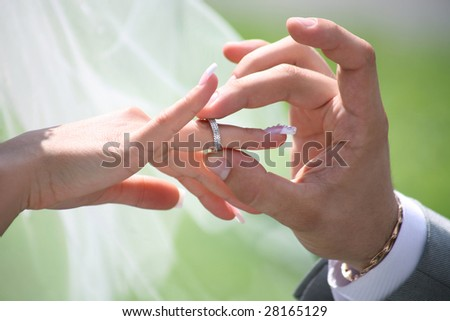 Close-up of groom?s hand putting wedding ring on bride?s finger - stock photo