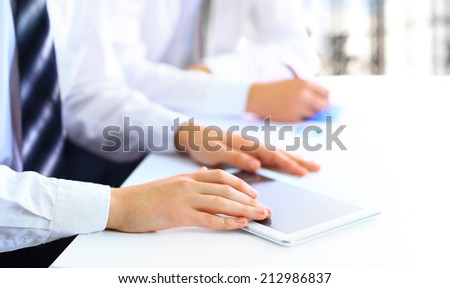 Close up of group of business people working at the office - stock photo