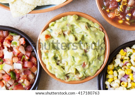 Close up of guacamole surrounded by pico de gallo and salsa, top down view - stock photo