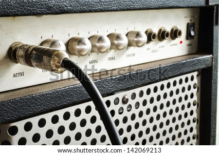 Close-up of guitar amplifier with jack cable - stock photo