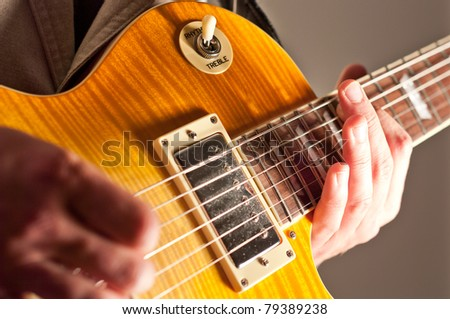 Close up of guitar with hand - stock photo