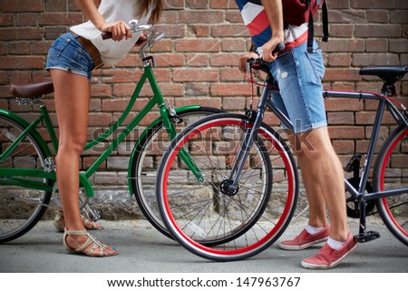 Close-up of guy and girl legs with bicycles against brick wall - stock photo