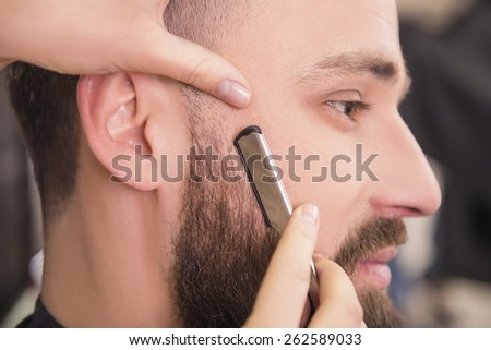 Close-up of hairdresser shaving an old-fashioned razor of satisfied client in professional hairdressing salon. - stock photo