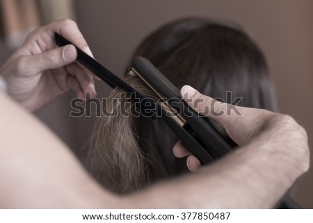 Close up of hairdresser using a hair straightener - stock photo