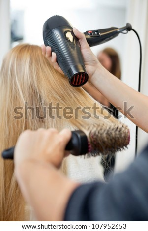 Close up of hairdressers hands drying long blond hair with blow dryer and round brush - stock photo