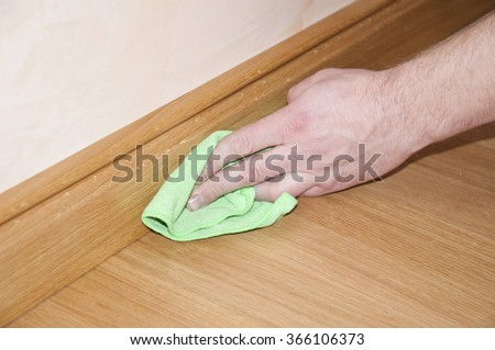 Close up of hand cleaning the wooden oak parquet floor and skirting board  - stock photo