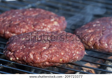 close up of hand formed hamburger patties on an outdoor grill with hickory wood chips for a smoky flavor - stock photo