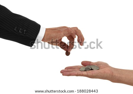 Close up of hand giving a penny to a cupped hand with change in it - stock photo