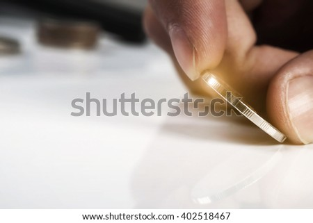 Close up of hand holding an coin with copy space, Business investment plan concept. - stock photo