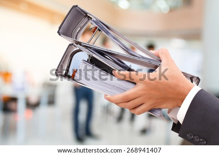 close up of hand holding binder in office - stock photo