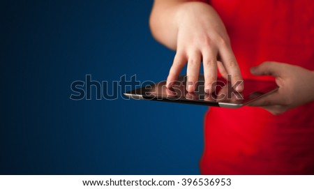 Close up of hand holding digital touchpad tablet device on background - stock photo