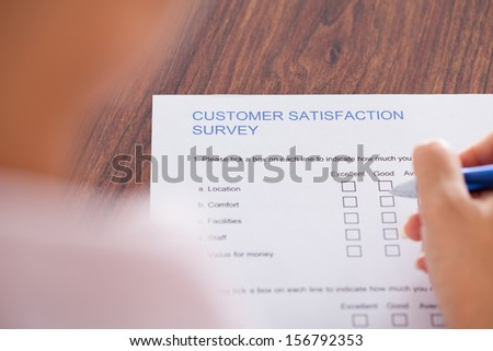 Close-up Of Hand Holding Pen Over Survey Form - stock photo